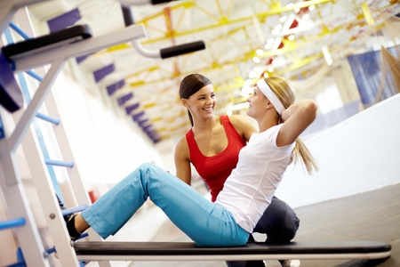 girl in sportswear: A girl pumping abdominal muscles in gym with help of her girlfriend