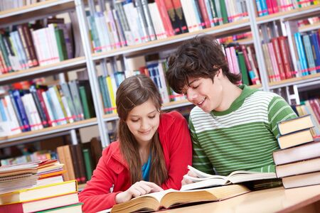 Portrait of teenage girl reading book with her classmate near by photo