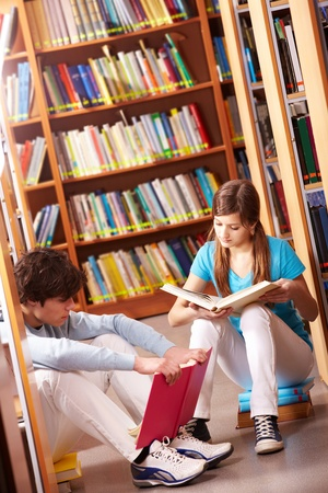 Portrait of teenage friends reading books in library photo