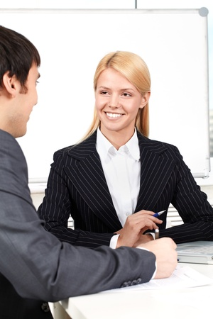 A businesswoman sitting at table and listening to a man Stock Photo - 9263155