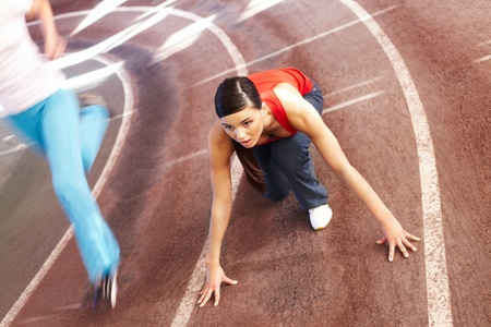 A young woman sprinter on the point of starting Stock Photo - 9263131