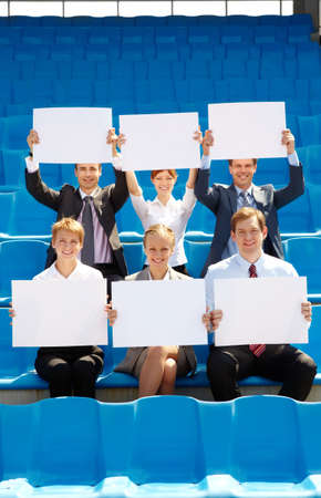 Portrait of several successful partners with blank papers sitting on stadium and looking at camera photo