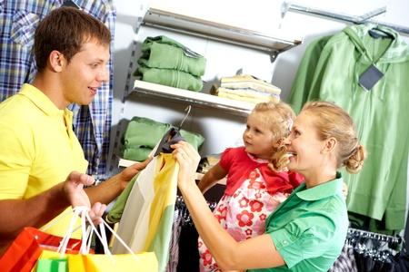 ni�os de compras: Una joven familia elegir ropa en la tienda