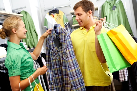 A wife choosing a shirt for her husband in the mall photo