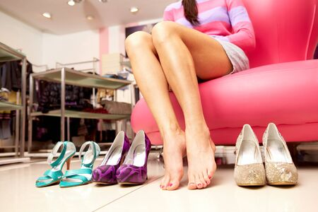 between: Female bare legs between pairs of shoes