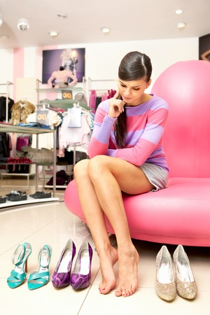 trying on: A young women sitting in shop and thinking what shoes to buy  Stock Photo