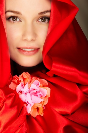 Gorgeous woman in red satin holds flower looking at camera Stock Photo - 9263316