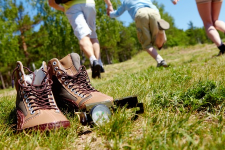 Image of pair of boots and compass on background of people running down green grass photo
