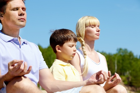 Photo of three family members meditating on summer day outdoors photo