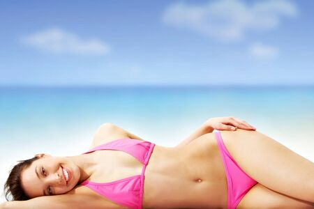 girl lying: A young girl sunbathing on the beach Stock Photo