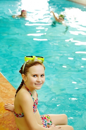 foreground: Photo of happy girl in swimming pool smiling at camera