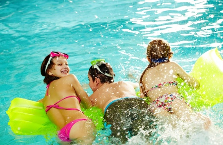 Photo of happy friends splashing water swimming in pool photo