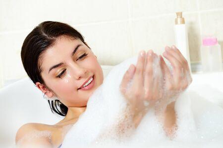 pleasant: Image of serene woman having pleasant bath with foam