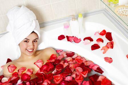 salud sexual: Retrato de una mujer feliz en agua rodeado de p�talos de rosas