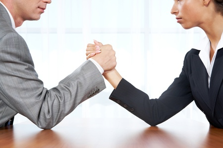 male arm: Portrait of business competitors doing arm wrestling and looking into each other's eyes