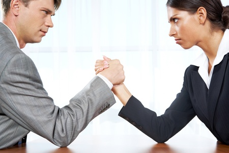 competitor: Portrait of business competitors doing arm wrestling and looking into each other's eyes