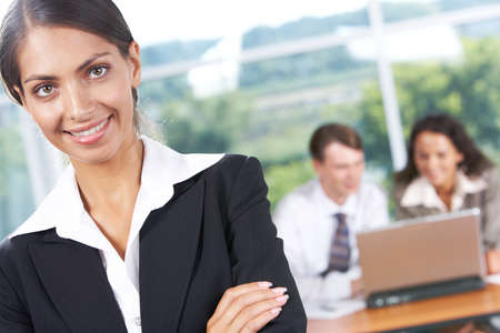 Portrait of successful business lady looking at camera with smile on background of her partners at work photo
