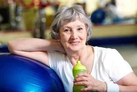 aktywność fizyczna: Portret kobiety wieku z butelka wody przez niebieski ball