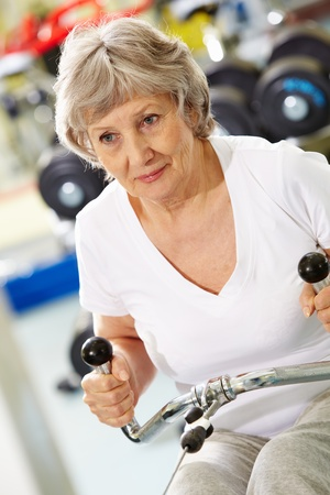 Photo of active woman pumping muscles on special equipment photo