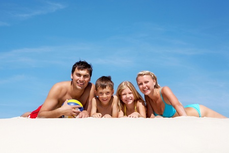 happy family lying on sand on summer vacation photo