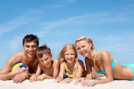 happy family lying on sand on background of blue sky photo