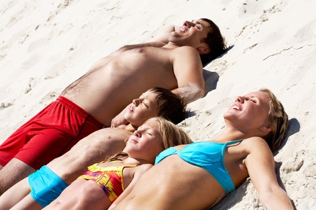adult sisters: Photo of happy family lying on sand and sunbathing