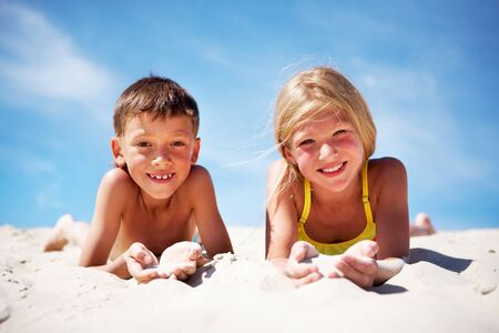 vacation: happy siblings lying on beach and playing with sand on summer vacation