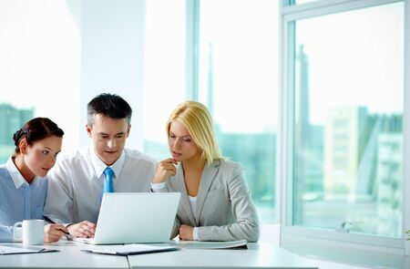 business man laptop: Retrato de varios colegas mirando la pantalla del port�til en la Oficina