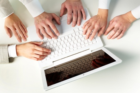 Human hands on keypad of laptop at workplace photo