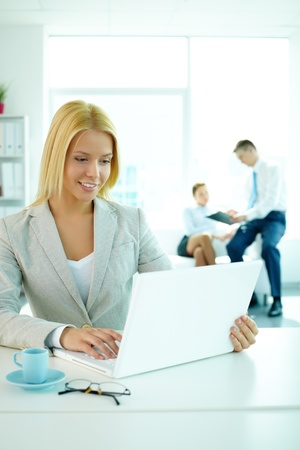 Portrait of pretty secretary looking at laptop screen in working environment Stock Photo - 9298612