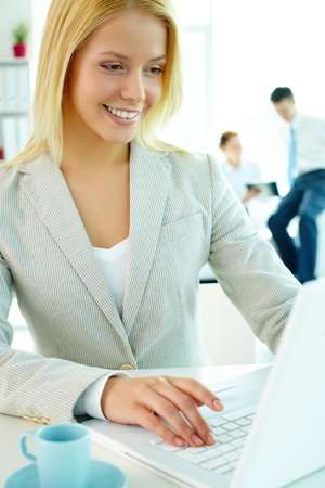 Portrait of pretty secretary looking at laptop screen in working environment Stock Photo - 9298635