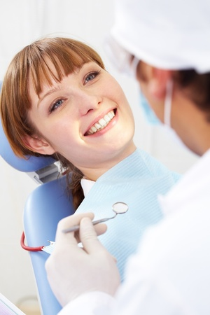 dentists clinic: Image of smiling patient looking at the dentist with mirror