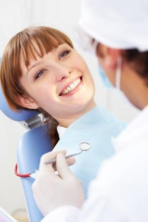 Imagen de sonreír paciente mirando el dentista con espejo