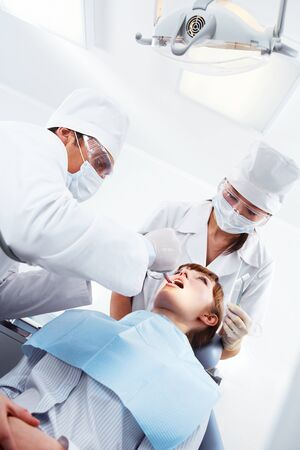 Image of patient sitting on dental armchair with doctor and nurse near by  photo