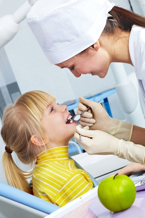 Image of dental checkup given to little girl by dentist  photo