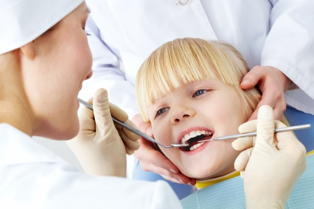 Image of little girl having teeth checked by doctor and assistant photo
