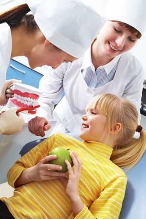 Photo of dentist teaching care dental hygiene little girl with assistant near by  photo