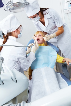 Image of little girl healing her teeth in dentists office photo
