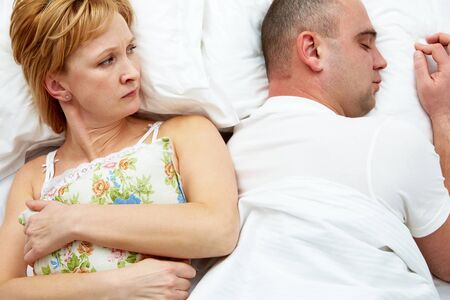 resentful: Photo of displeased wife holding pillow looking her husband