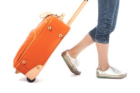 Foto della femmina elegante che trasporta la valigia rossa