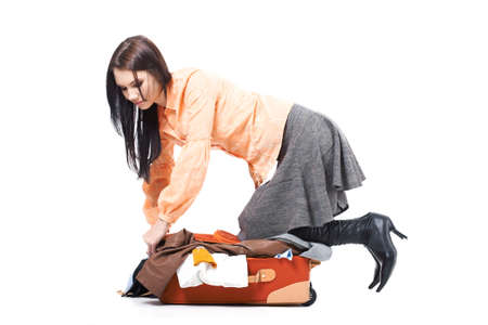 holdall: Pretty woman tries to close her suitcase