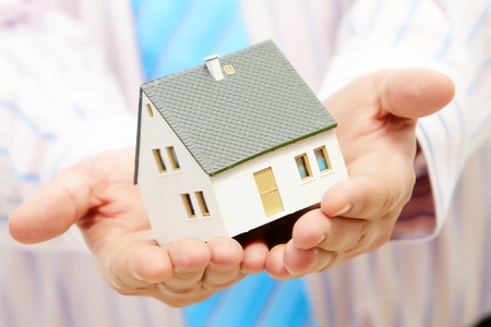 building home structure: Close-up of toy house model in male hands