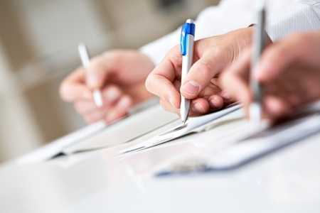 place to learn: Image of row of people hands writing on papers at seminar Stock Photo