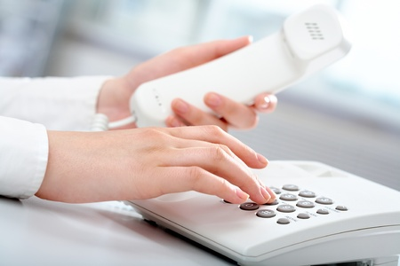phone receiver: Close-up of receptionist making a phone call