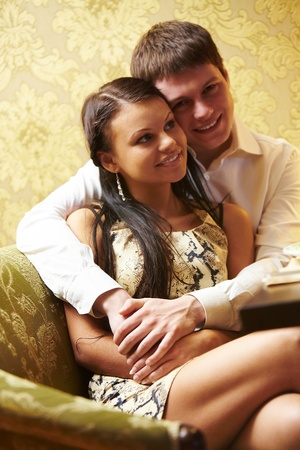 Portrait of boyfriend embracing his girlfriend and sitting on the sofa together  Stock Photo - 9319407