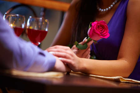 amorous woman: Close-up of female holding a red rose and her hand over male hand at  Valentine�s day     Stock Photo