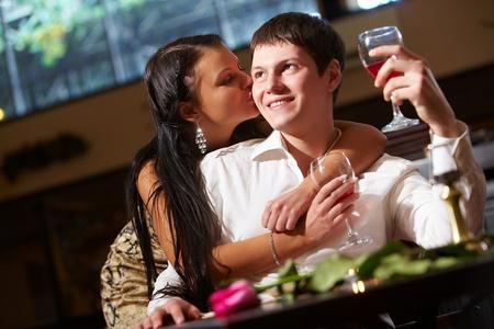 Portrait of woman kissing her boyfriend in the restaurant photo