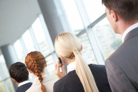 Rear view of business woman calling among her colleagues photo
