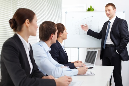 Three businesspeople listening to a teacher at the seminar  Stock Photo - 9319734