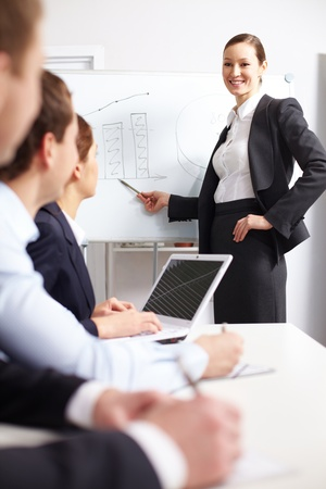 A businesswoman pointing at whiteboard before her colleagues  photo